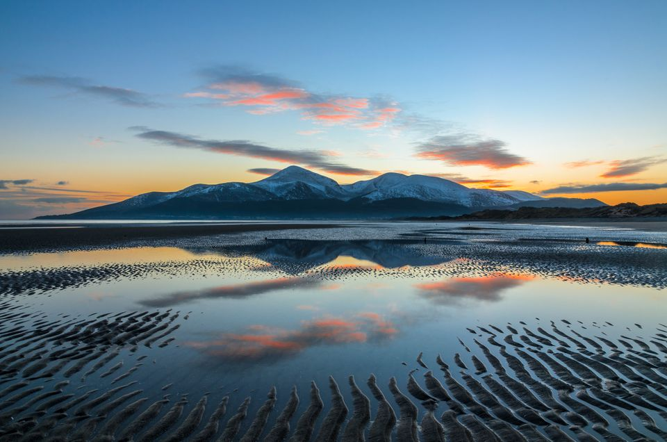 mourne mountains at sunset reflected in the ocean