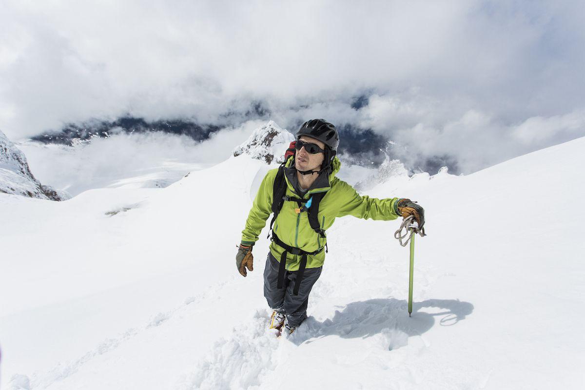 A man walks through deep snow on a mountain ridge while carrying an ice axe.