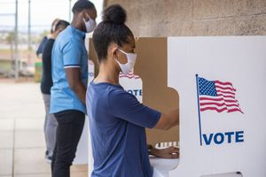 a brown-skinned woman and a man wearing maskgs at a voting booth