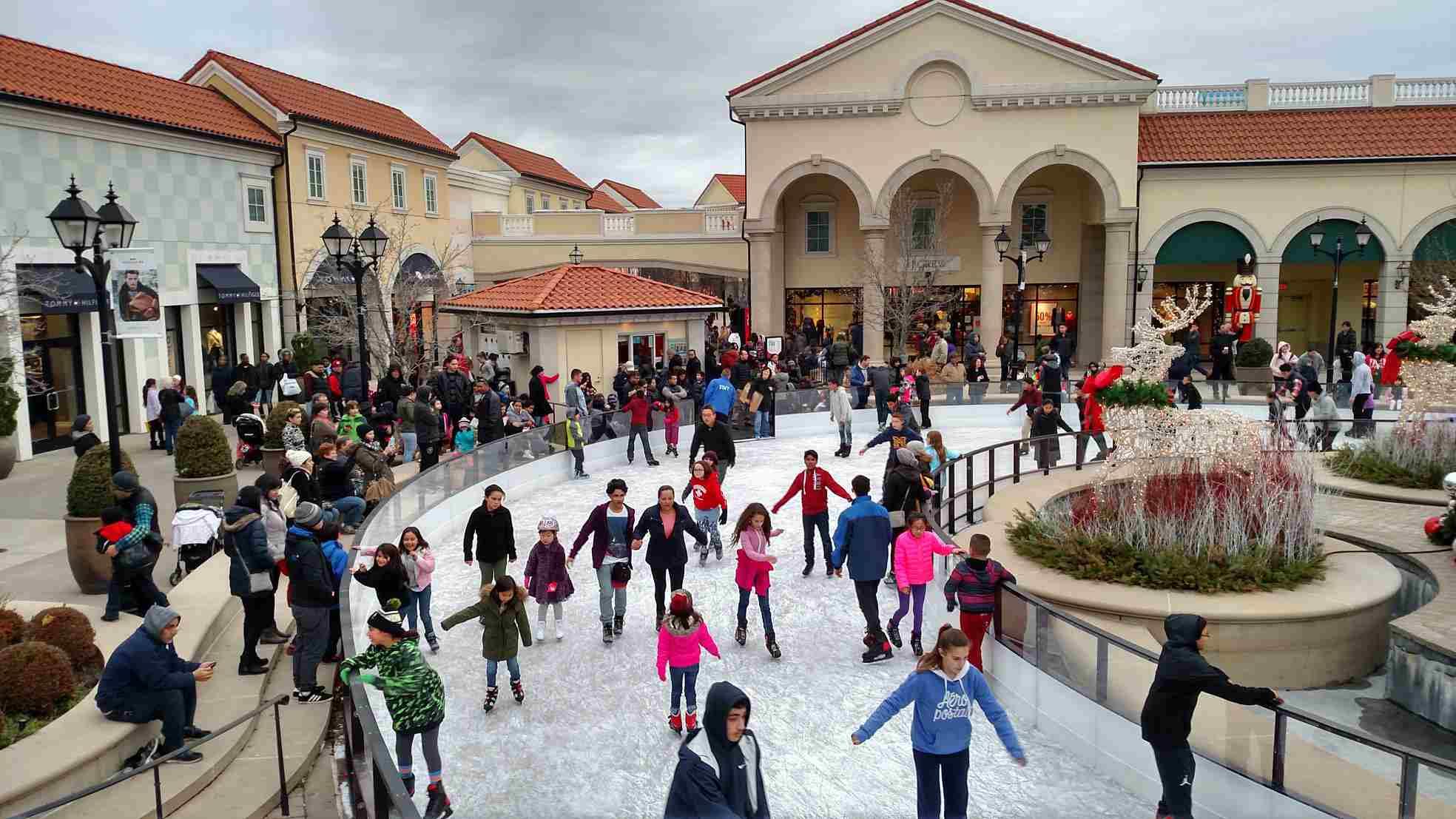 Varias familias y niños patinando alrededor de la pista de hielo Deer Park