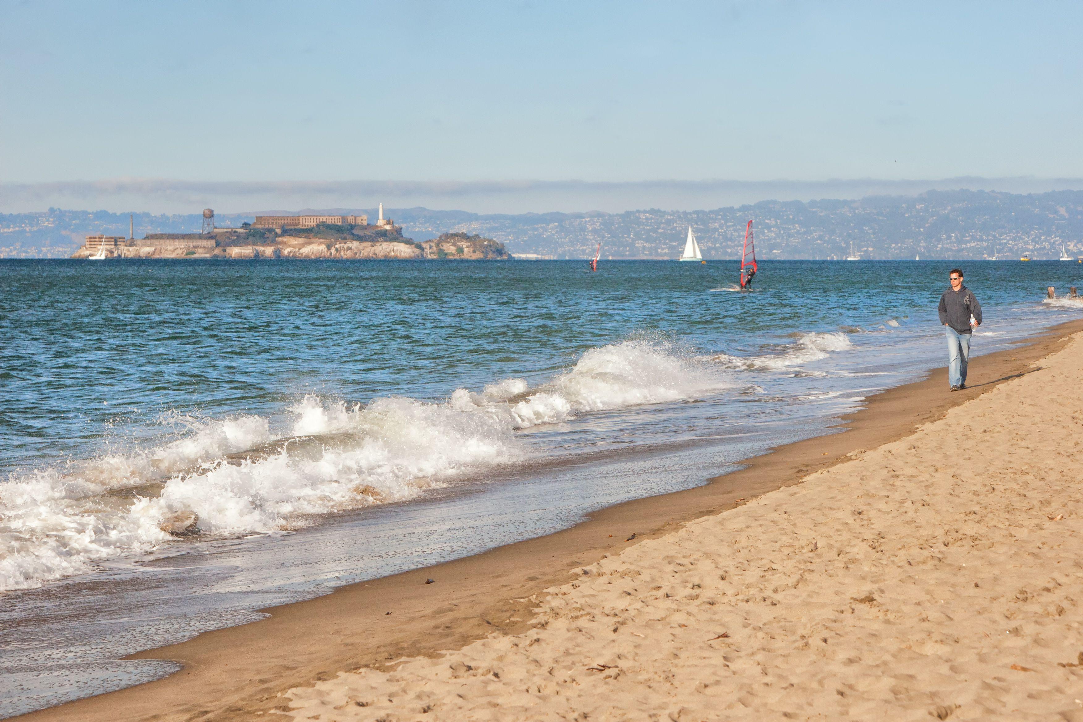 Man walking on beach with Alcatraz behind him
