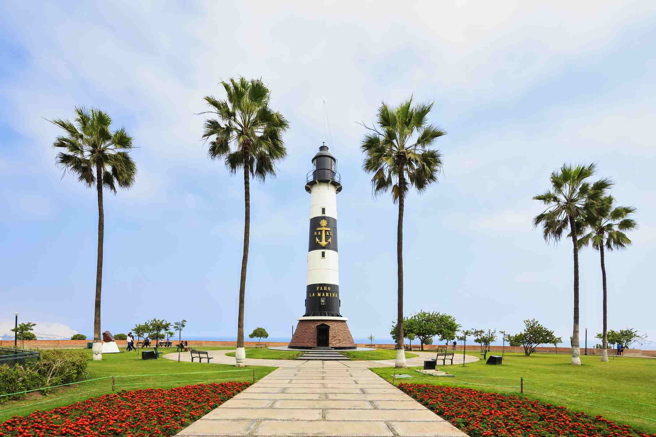 Miraflores Boardwalk Lighthouse is striped, gilded with anchors, and flanked by palm trees