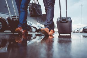 Two people walk with luggage through an airport parking lot