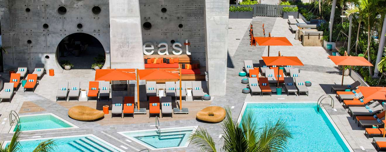 Courtesy of Aerial show of East, Miami pools with one rectangular pool and three, smaller polygonal pools. There are several orange umbrellas and orange and gray pool chairs