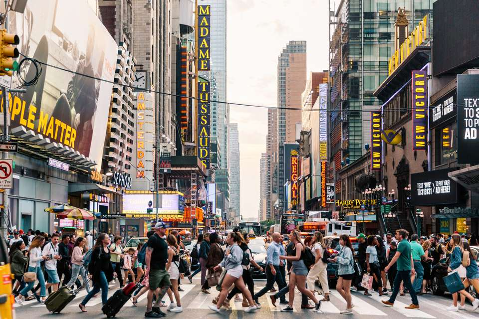 Crowds of people crossing street on zebra crossing in New York, USA