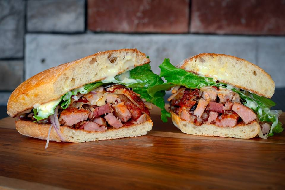Two halves of a porchetta sandwich next to each other on a wooden table. The sandwich is slow-smoked pork loin and bacon with roasted tomatoes, mayonnaise, red onion and lettuce.