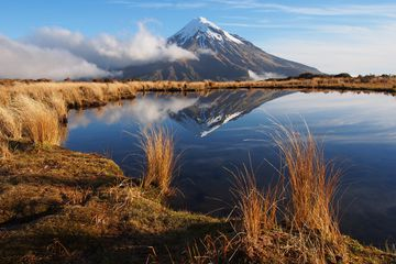 volcanic mountain reflected in lake with dry grassland and blue sky