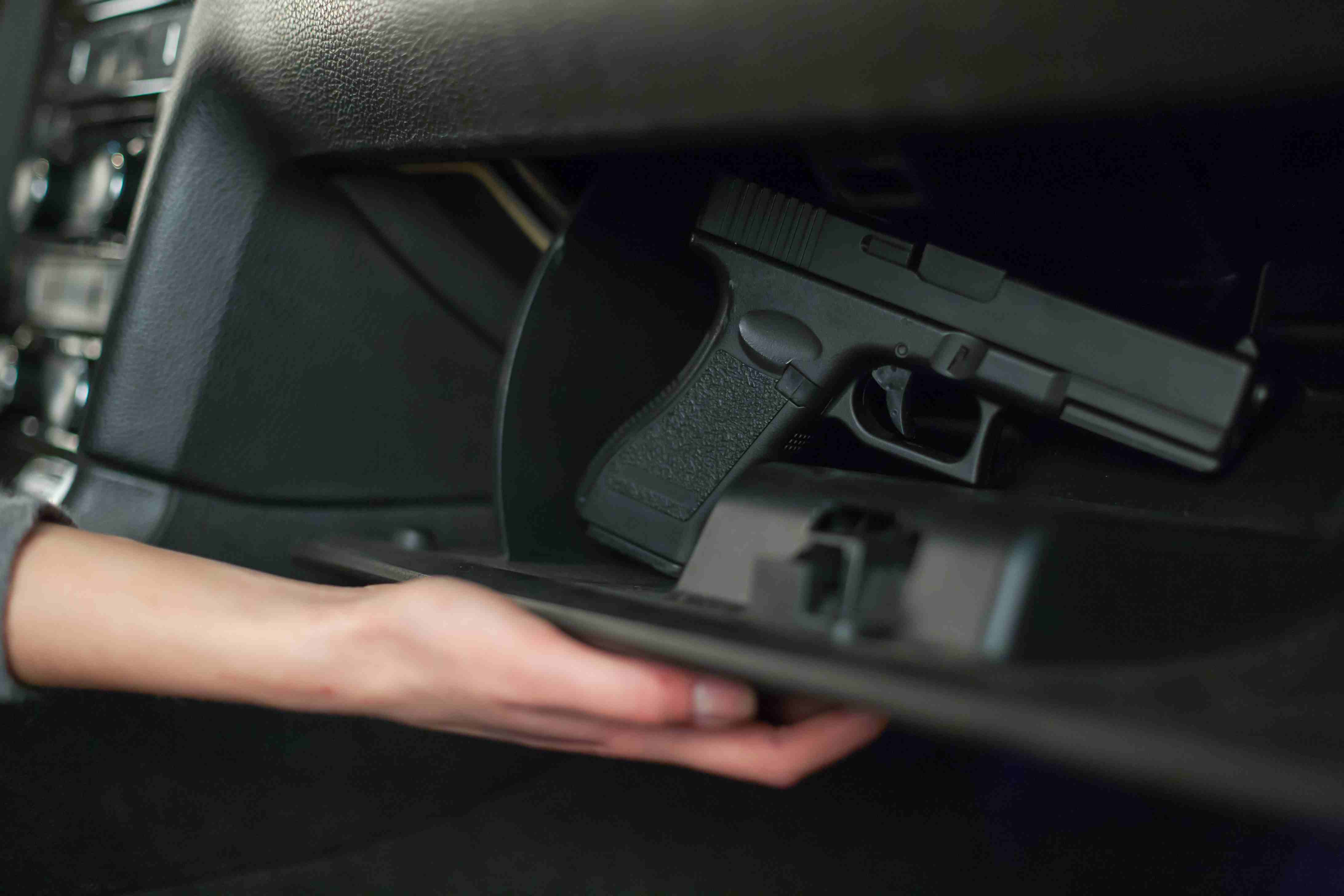 Closeup of hand pulling out a gun from a car's glove box