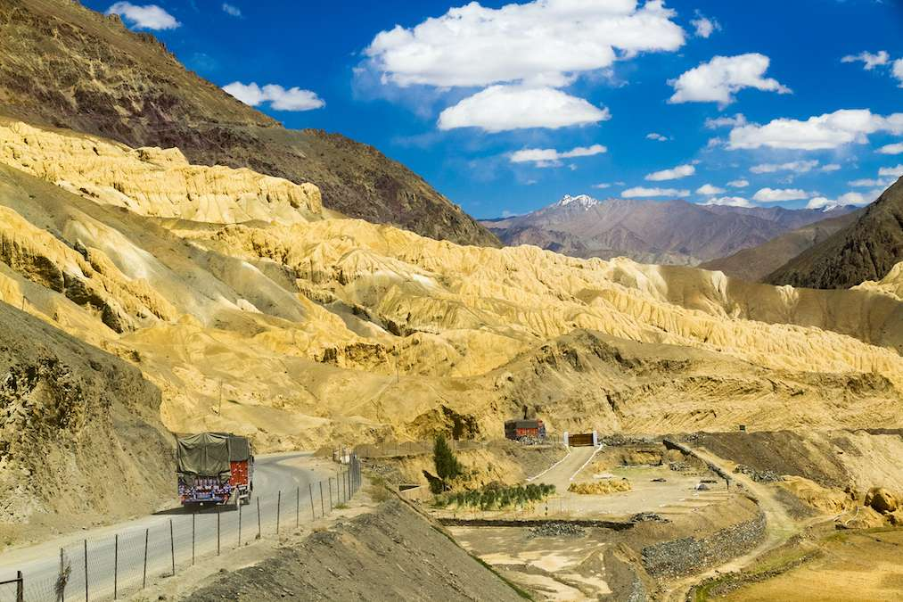 A truck drives along a lonely mountain road in Central Asia