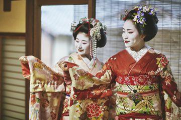 Portrait of Smiling Japanese Maiko Showing Kimono Sleeves