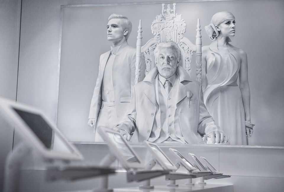 White and gray photograph of president Show sitting in an elaborate chair with Peeta and johanna flanking snow, looking in the distance. There is a series of six white tablets in a row perpendicular to the large photograph
