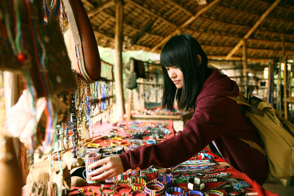 Woman perusing beaded jewelry in a market