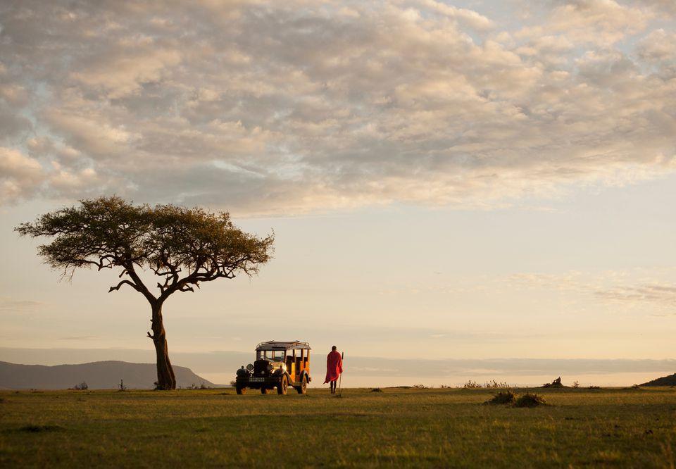 Guerrero masai se encuentra al lado de un vehículo de safari vintage en Kenia