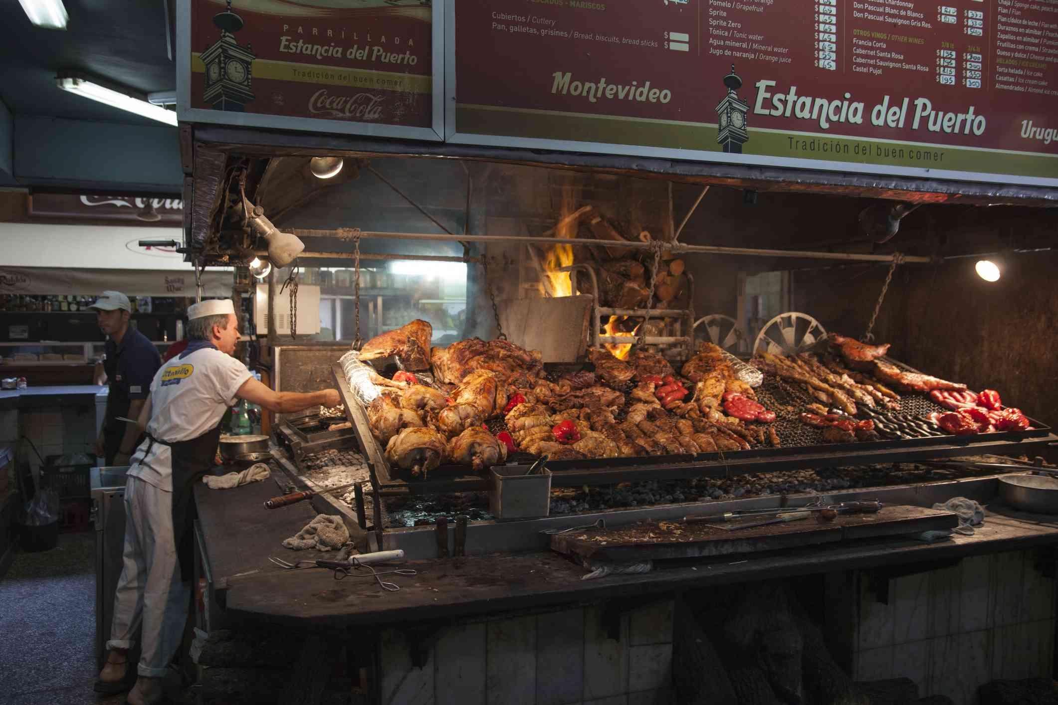 Chef grills steak and meat at Estancia del Puerto Parrilla type restaurant in Mercado del Puerto, ol