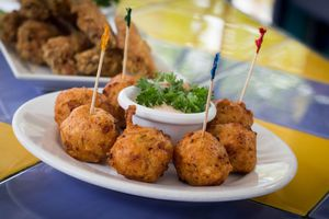 8 conch fritters in a circle on a plate with a small cup of sauce in the middle. Every other fritter has a toothpick in it
