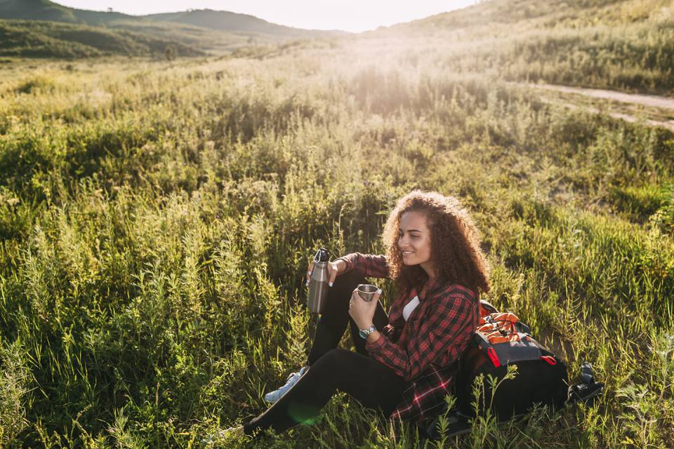 Teenage girl with thermos flask having a rest in nature