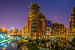 Night view of brick buildings alongside a water channel in the central Birmingham, England.