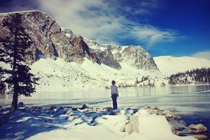 Woman standing with frozen lake and snowy mountain in Laramie, Wyoming