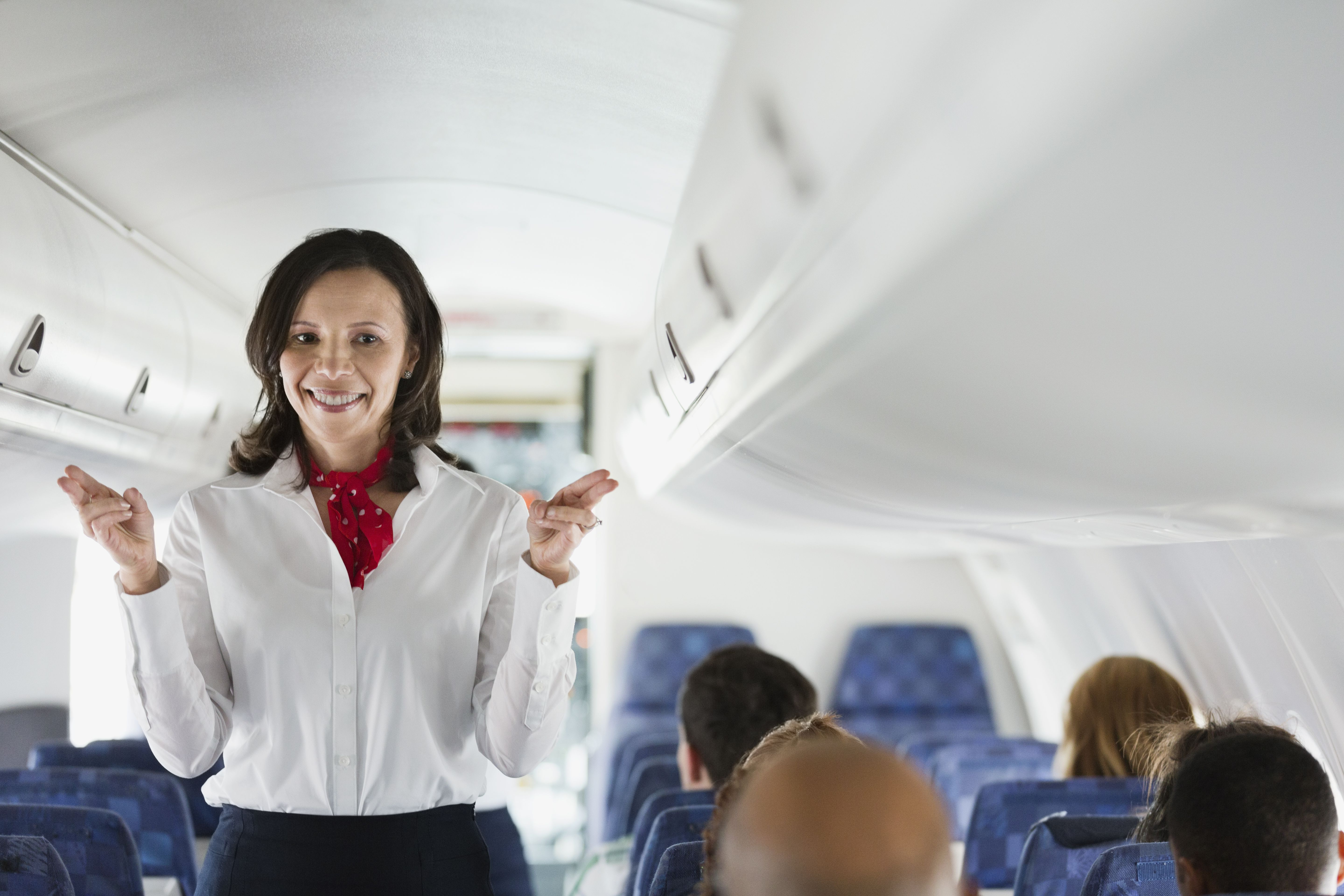 Flight attendant indicating exits in airplane