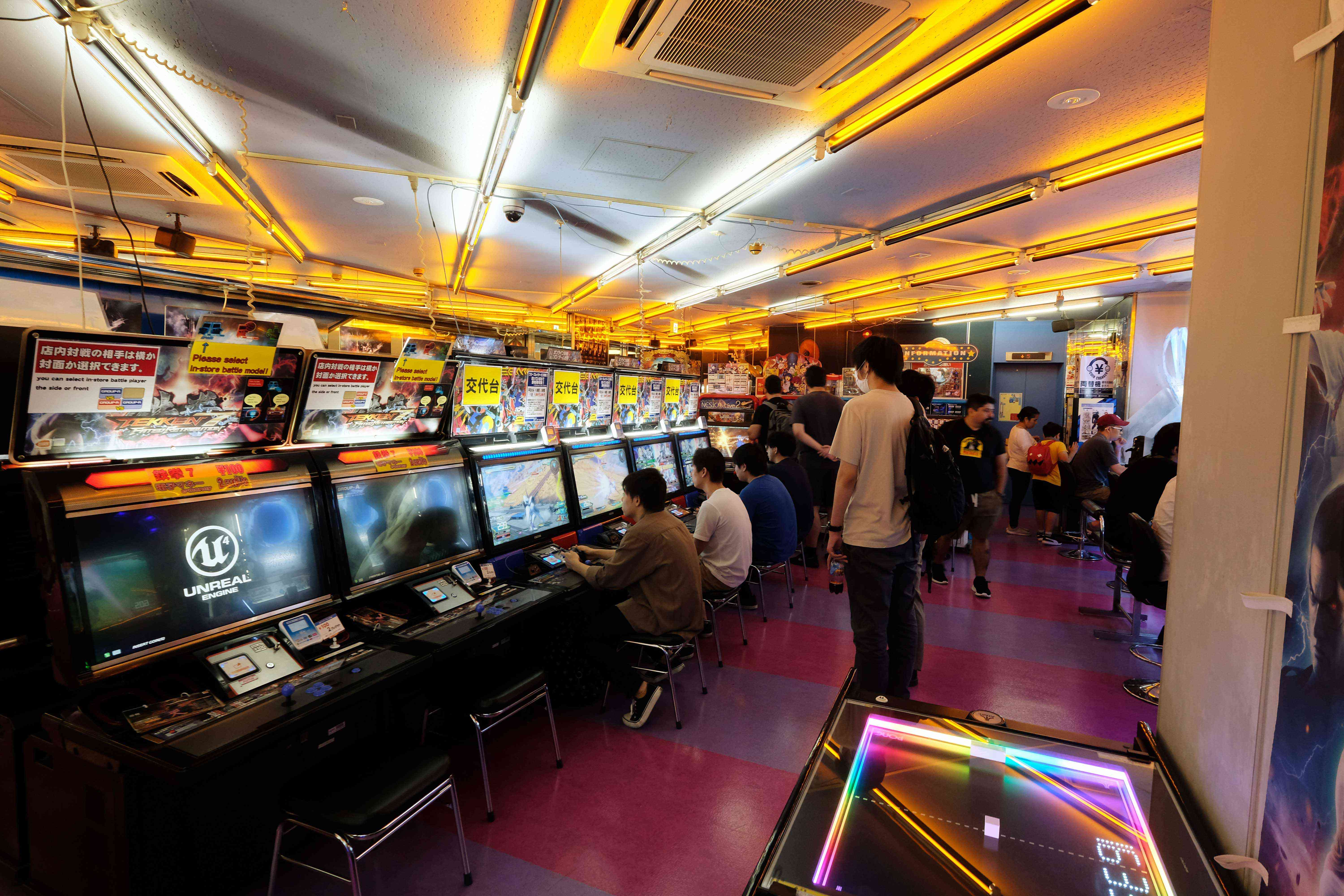 People playing games inside a large arcade