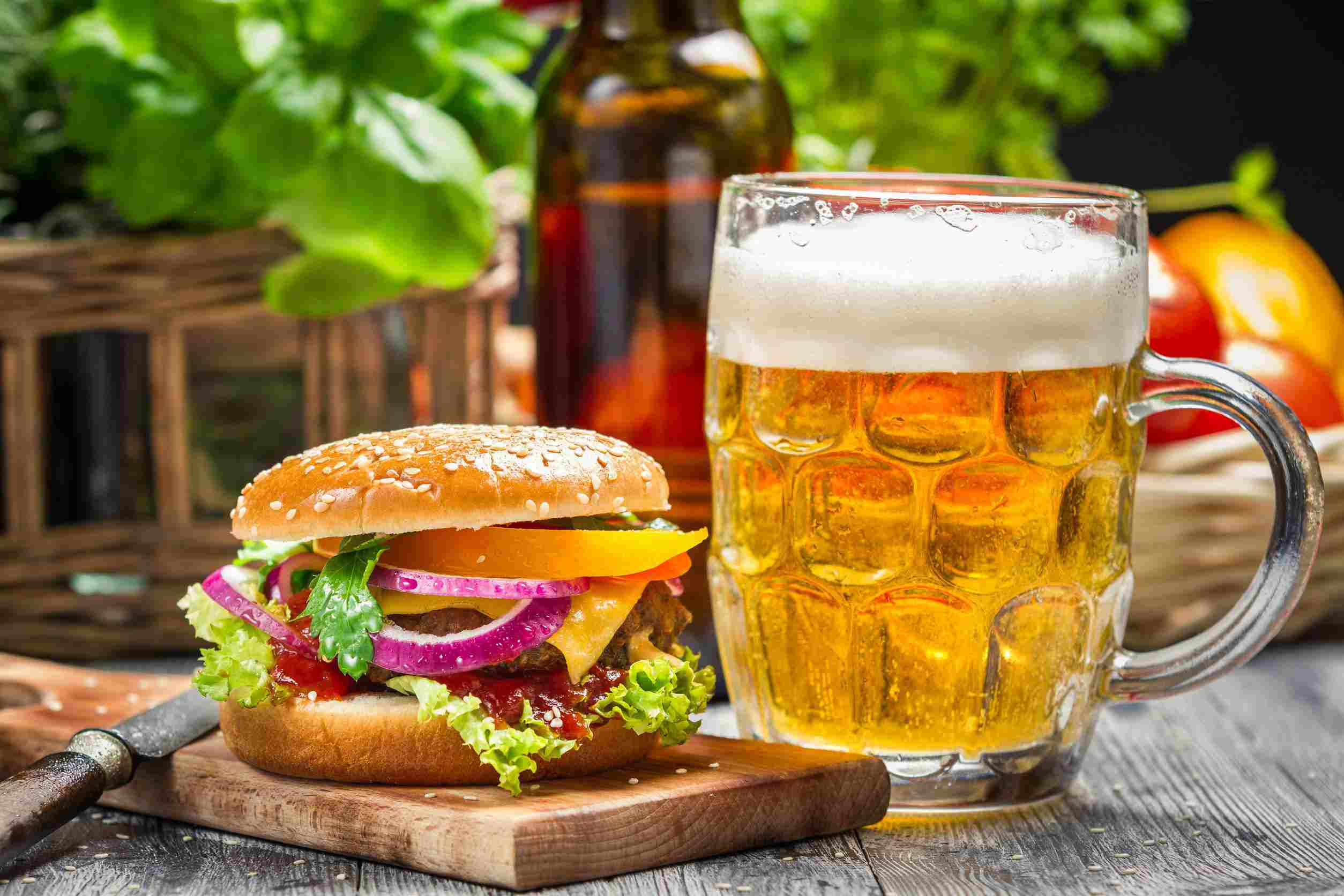 Cheese burger with red onions, lettuce, and ketchup with a sesame seed bun. To the right of the burger is a mug of lite beer