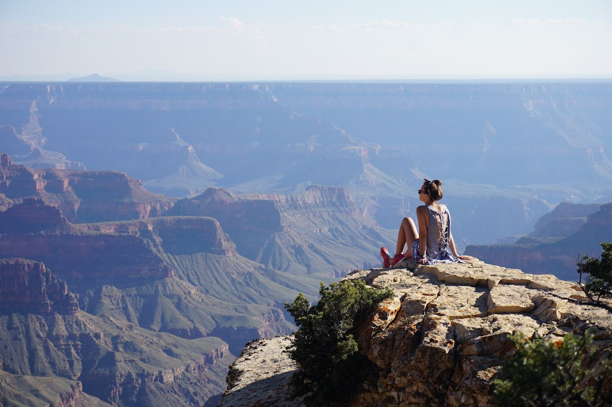 Woman sits on cliff overlooking Grand Canyon