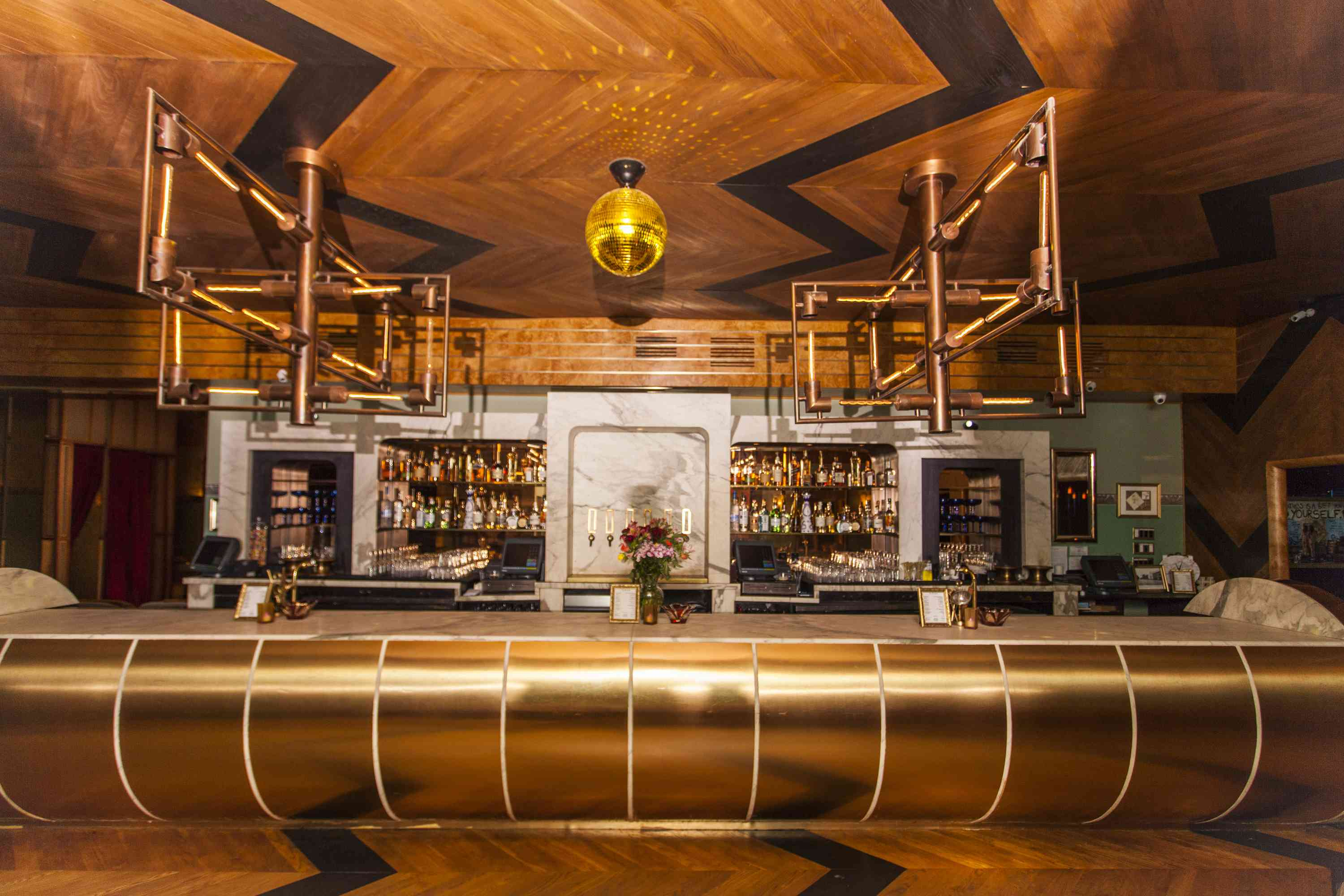 Metallic bar with a gold disco ball and industrial light fixtures