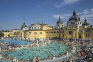 A busy outdoor thermal bath with classic Hungarian architecture