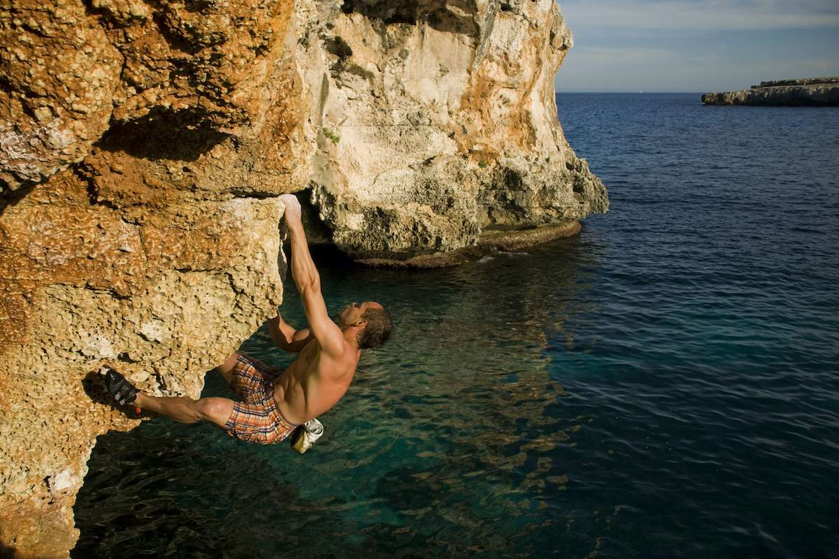 A rock climber hands above the waters of the Mediterranean Sea