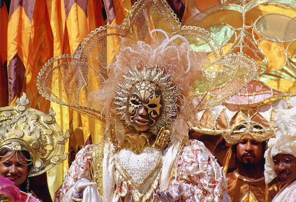 Carnival dancers wearing traditional costumes in pastel colors and gold in Trinidad, Caribbean