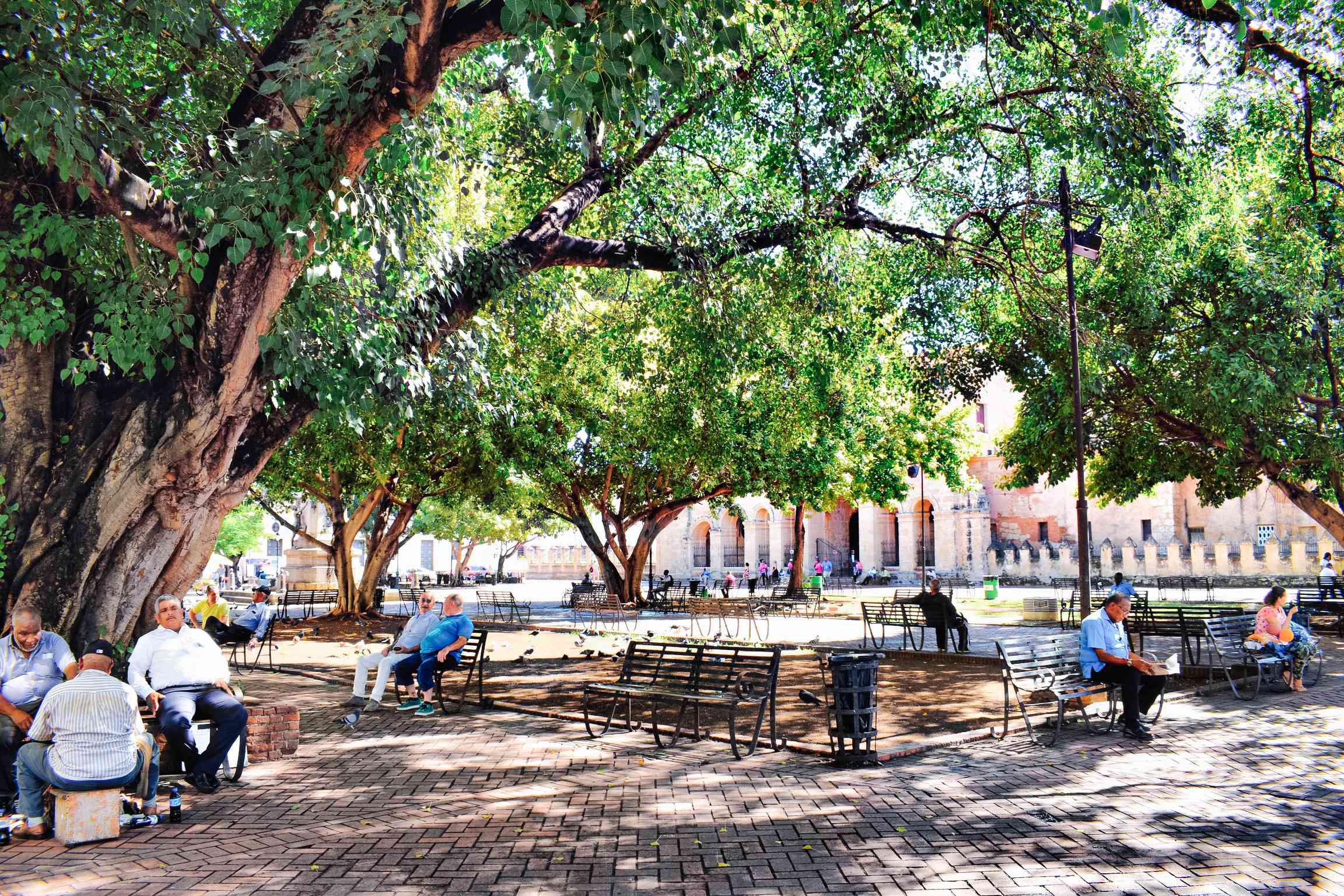 People sitting in a shaded courtyard in Parque Colon