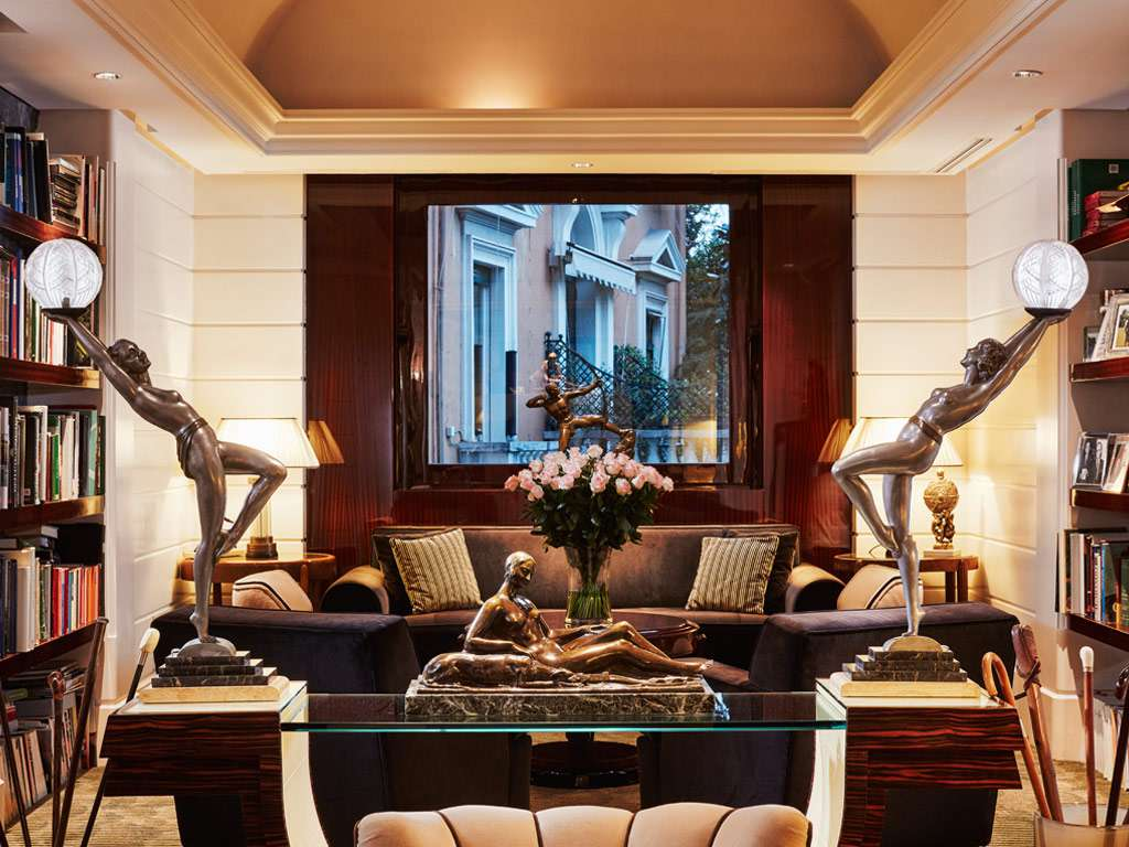 Lounge at hotel lord byron with four sculptures placed around the room and books on the wall