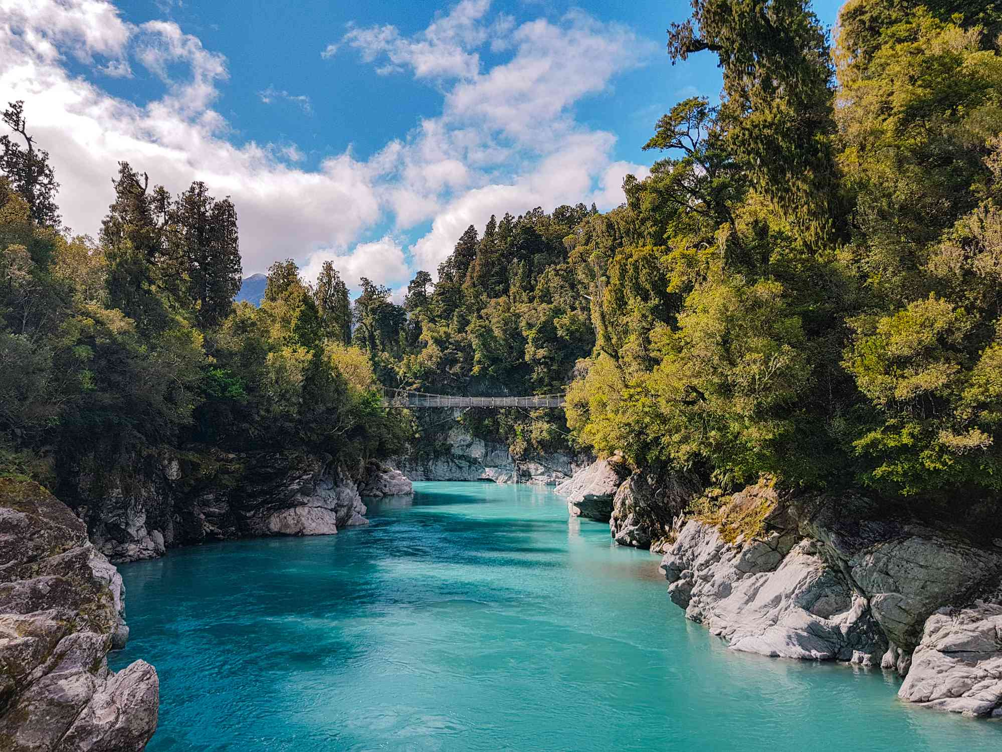 turquoise river surrounded by rocks and trees with a swing bridge in distance
