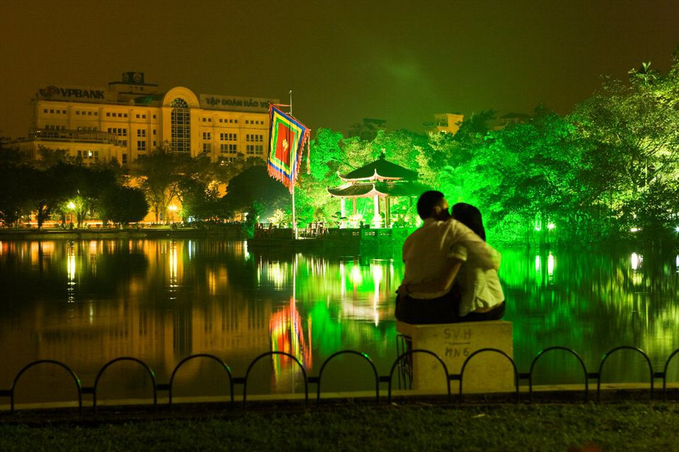 Couple snuggling in front of Hoan Kiem Lake, Vietnam