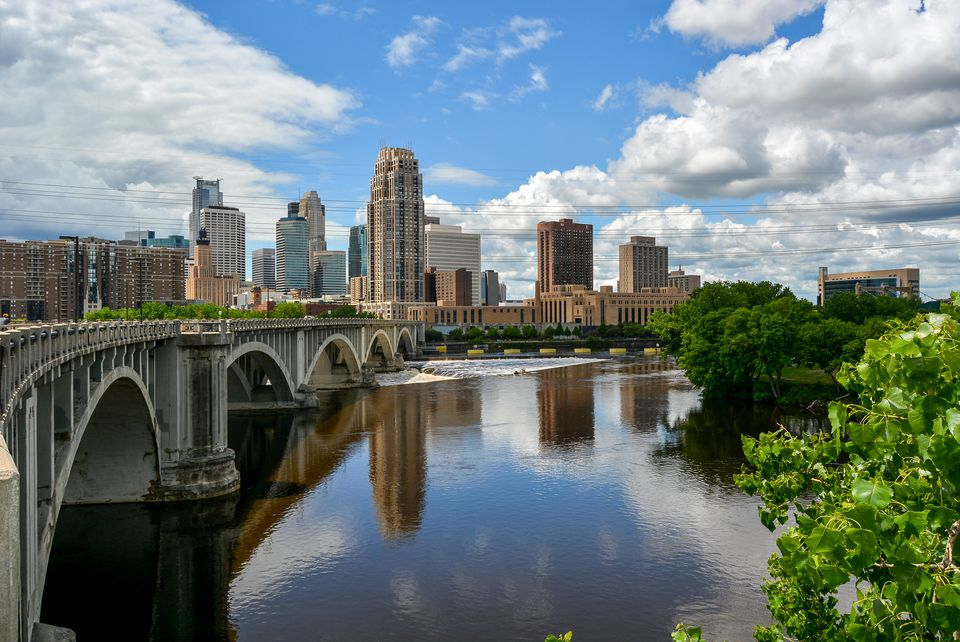 Arch Bridge Over River By Buildings in Minneapolis