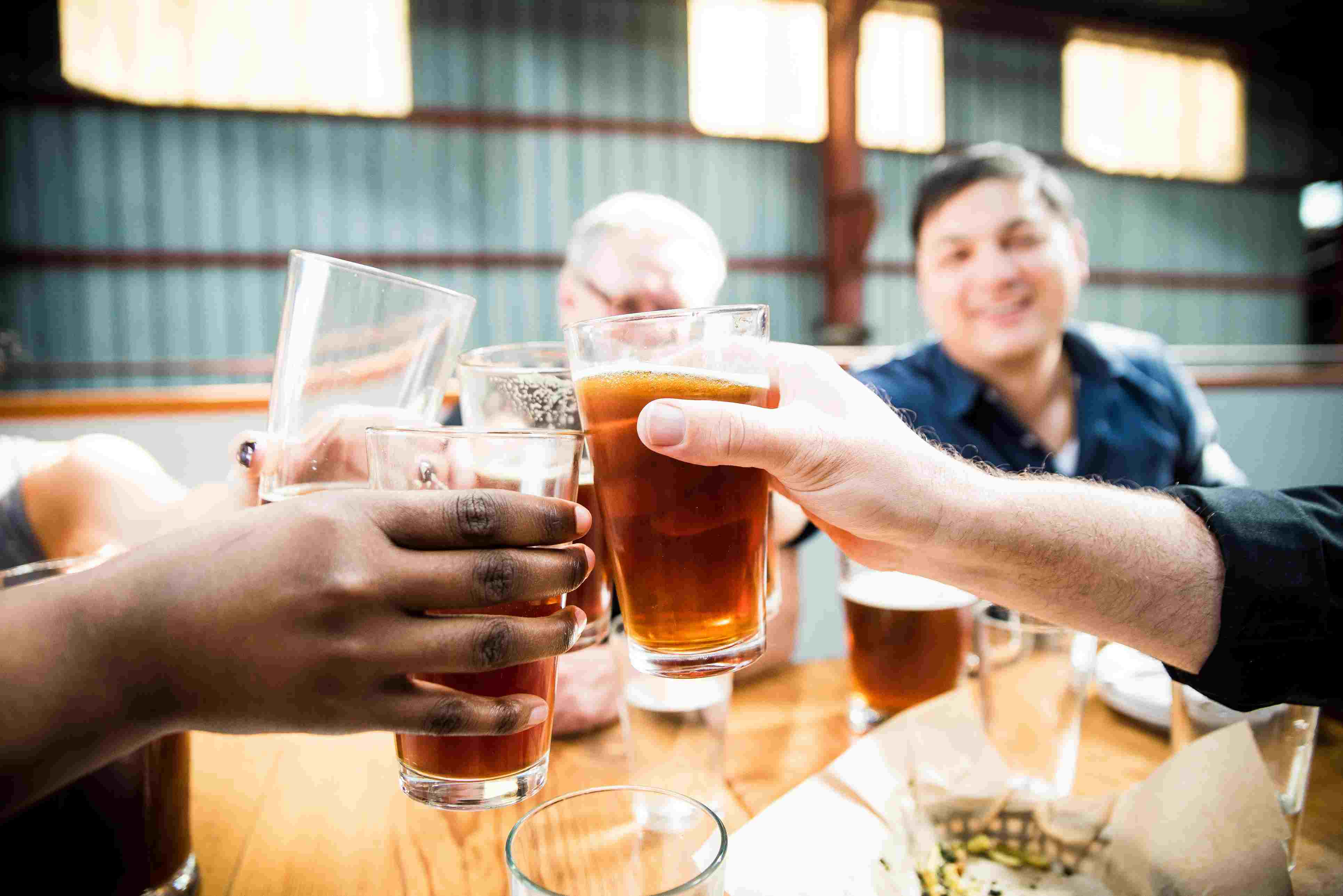 Close-up Of People Toasting With Beer