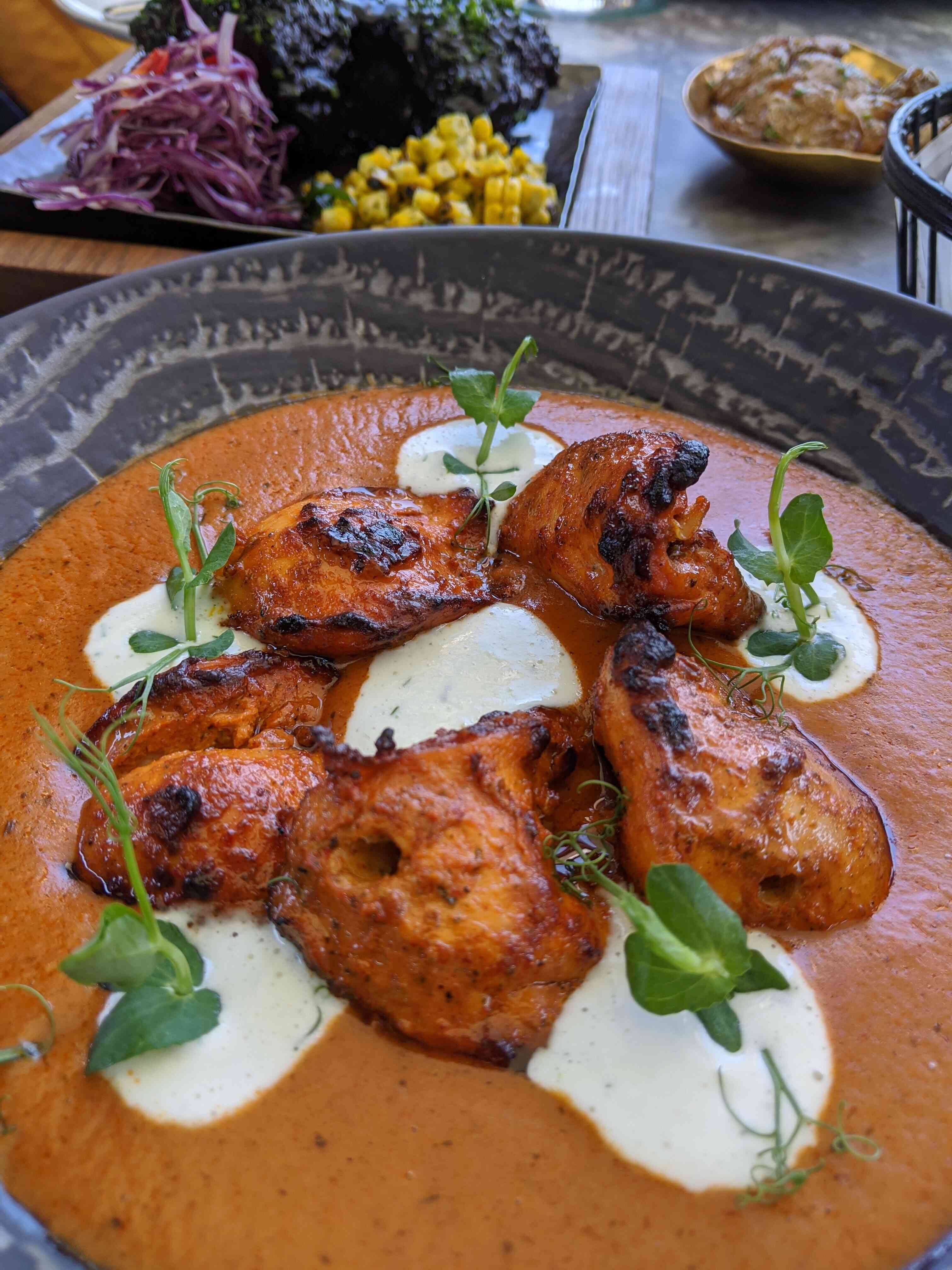red indian currey with dollops of cream and five large piece of chicken arranged in a circle and garnished with five green sprouts