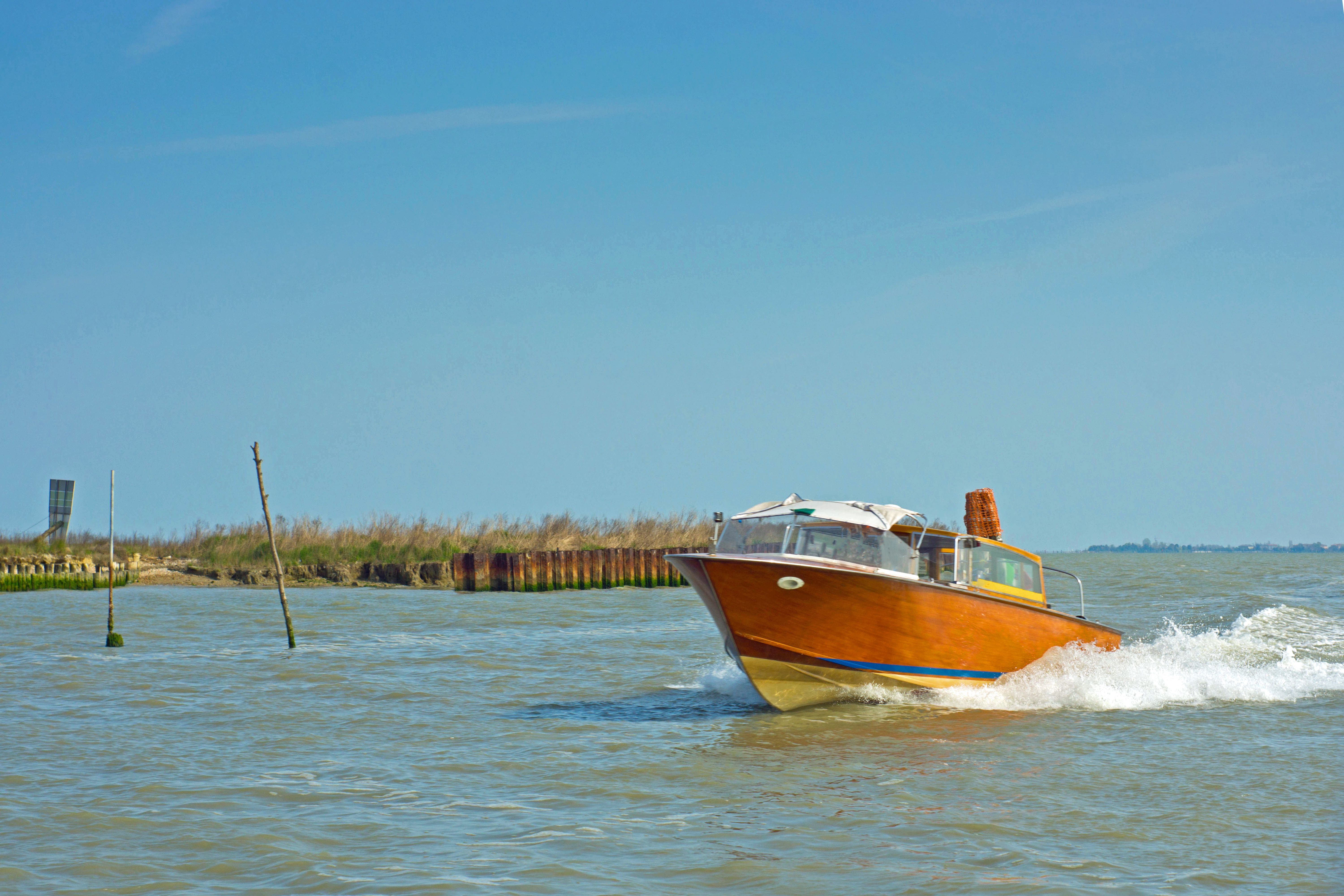 Water taxi going to Venice airport. This is one of the wooden hulled 50s style taxis and is seen on its way through the allotted route marked by wooden stakes either side.