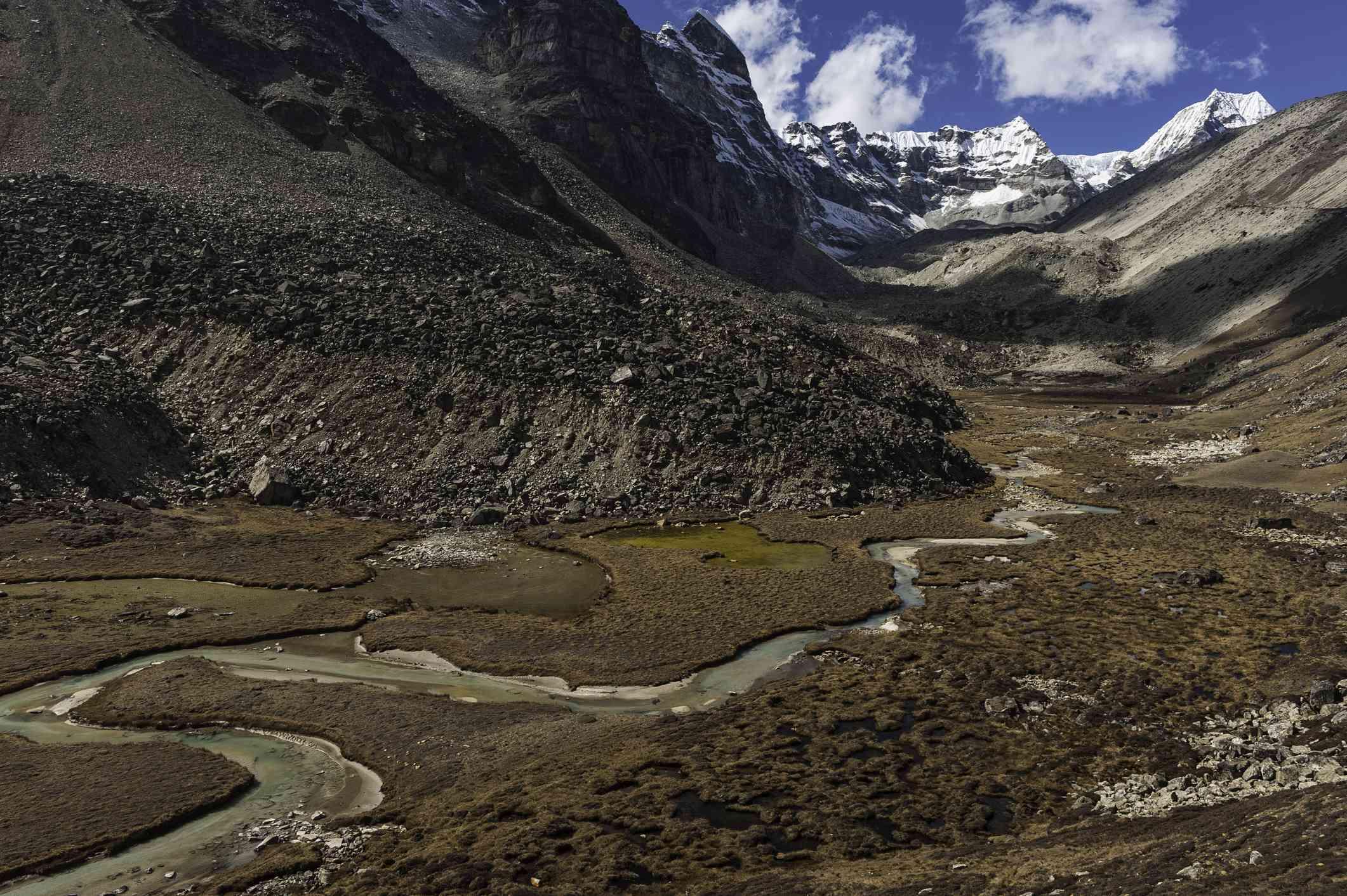 río que atraviesa un valle marrón con montañas nevadas detrás , Monte Langtang cubierto de cerda