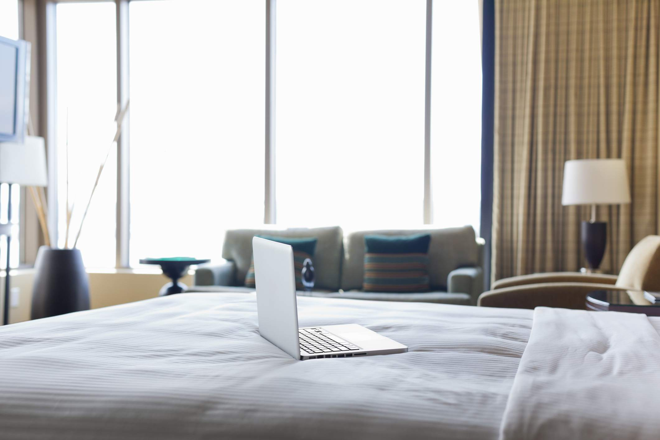 Laptop computer on bed in empty hotel room.