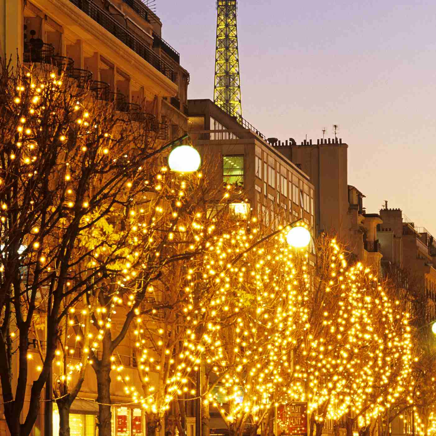 Holiday lights on Avenue Montaigne with the Eiffel Tower in the distance