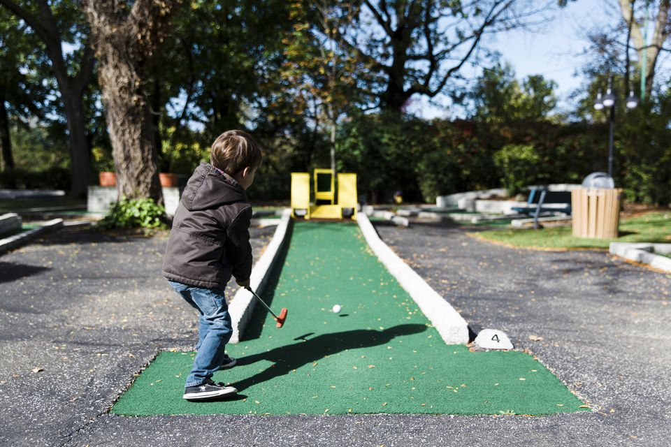 Boy playing minigolf