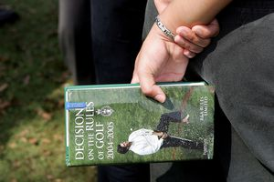 person holding a golf book