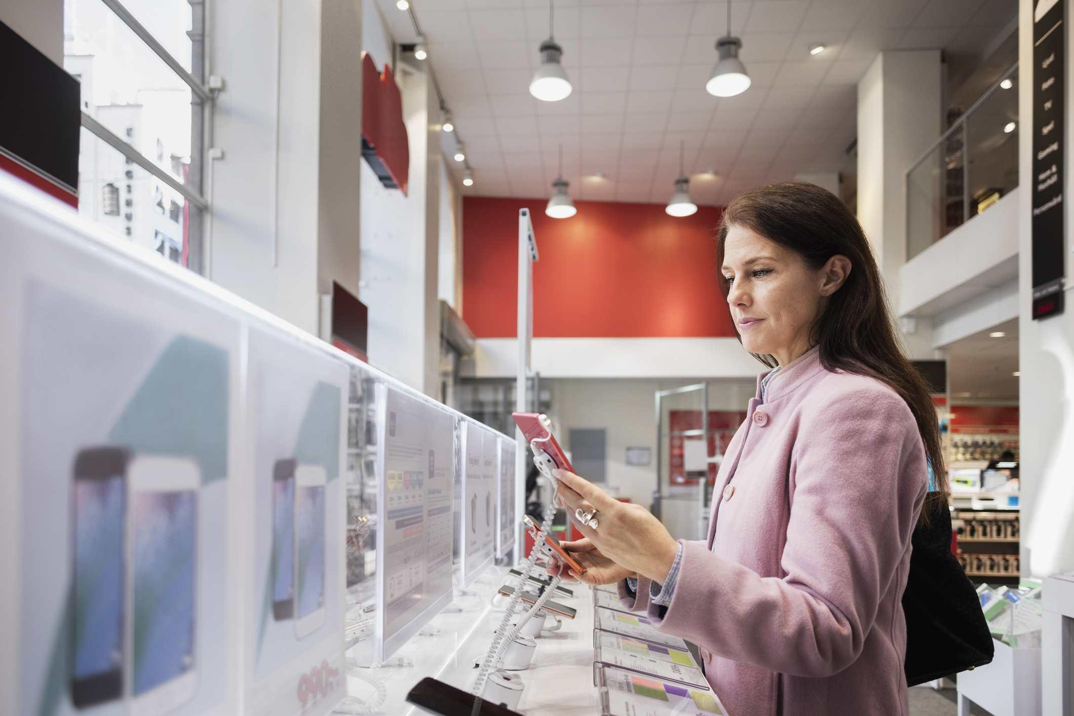 Vista lateral de la mujer que usa un teléfono inteligente en la tienda