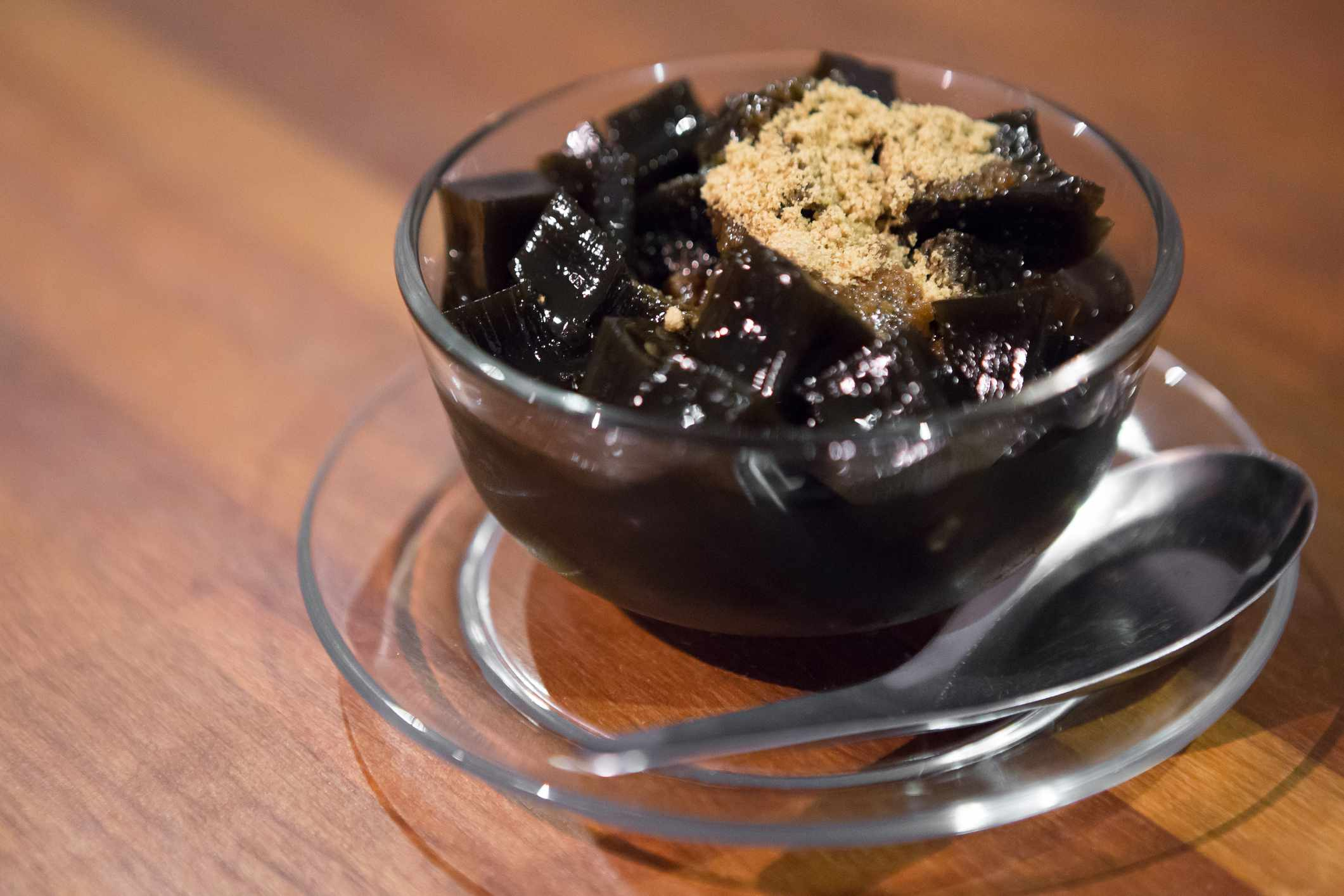 Close up of black jelly cubes with a tan powder in a clear cup on a wooden table