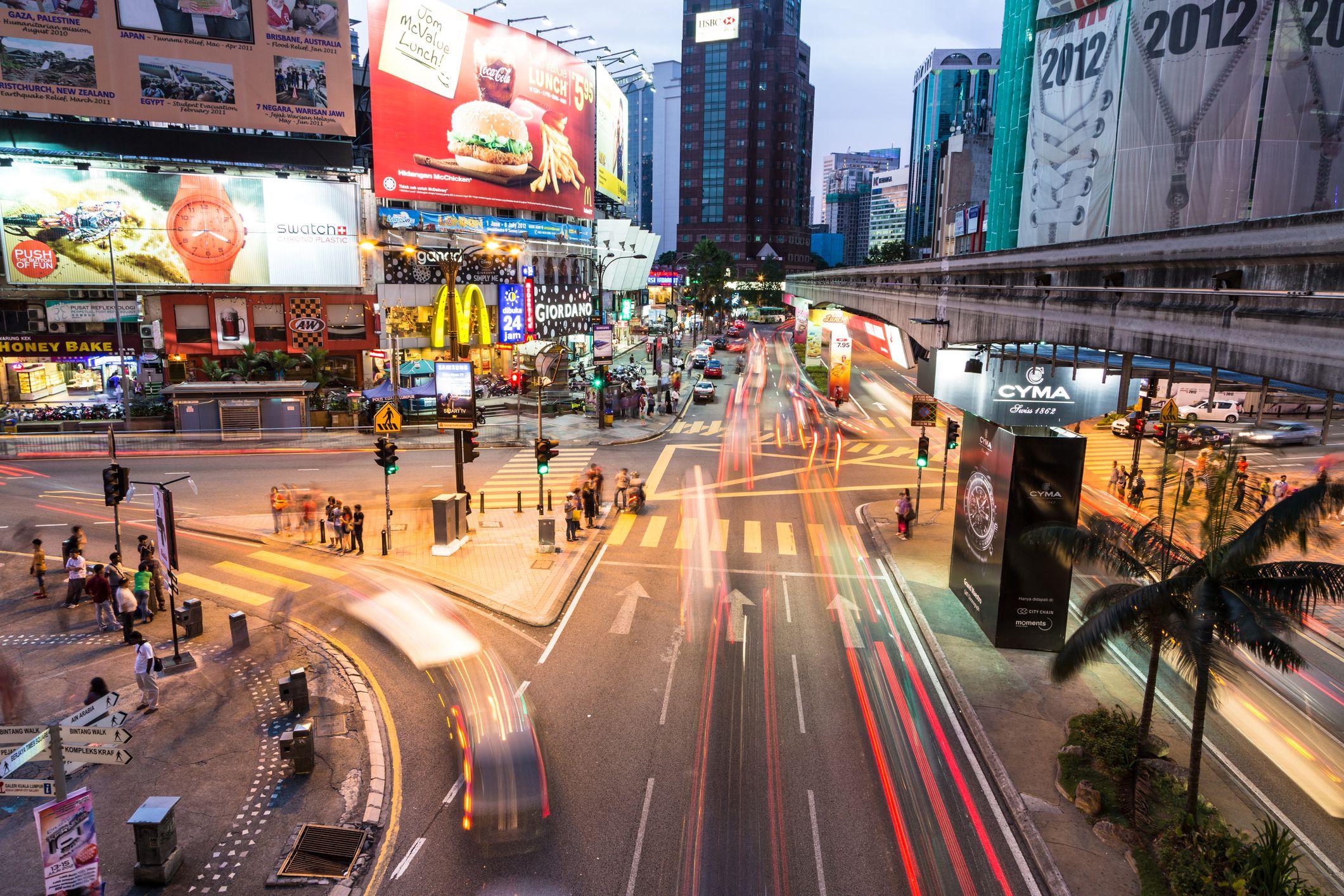 Cars rush at night through the Bukit Bintang intersection in the Kuala Lumpur City Center.
