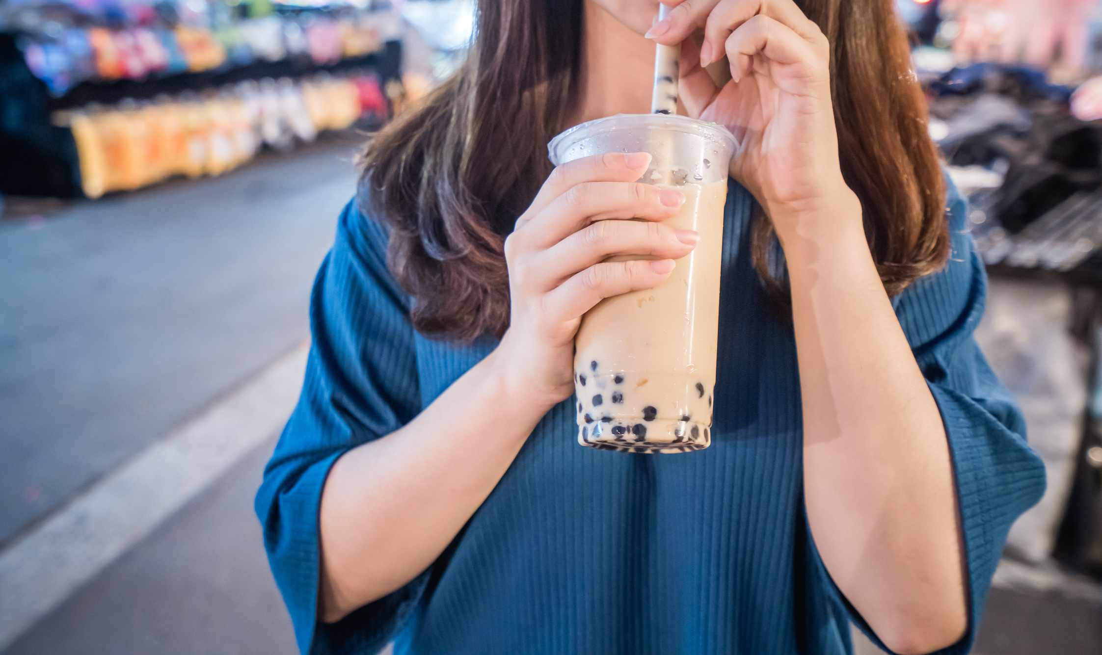 A young woman is drinking a plastic cup of bubble milk tea with a straw at a night market in Taiwan, Taiwan delicacy, close up.