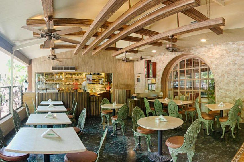 Restaurant with warm tones and and green metalwork chairs