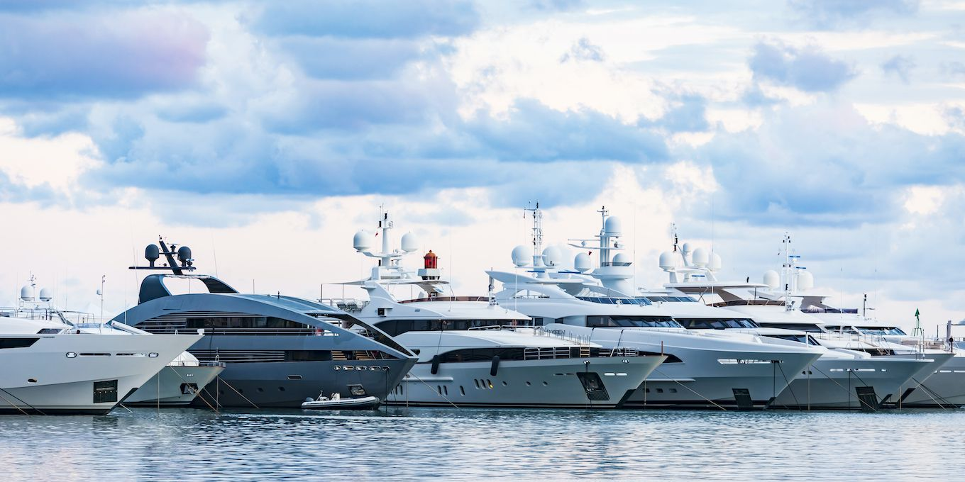 a row of luxury yachts parked next to one another in a harbor.