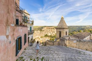 Woman climbing the stairs of Santa Maria delle scale church, Ragusa Ibla in the background, Ragusa, Sicily, Italy, Europe